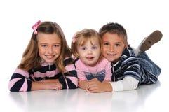 Enfants se trouvant sur l'étage et le sourire Photos stock