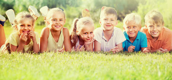 Enfants se trouvant sur l'herbe verte Images stock