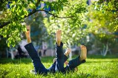 Enfants se trouvant sur l'herbe verte en parc un jour d'été avec le leur Photo libre de droits