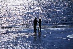 Enfants silhouettés sur l'eau Photo libre de droits