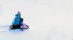 Enfants Sledding en bas de la colline de neige sur la vitesse rapide de traîneau Photos stock