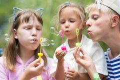 Enfants soufflant des bulles de savon Photo stock