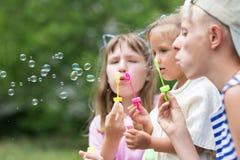 Enfants soufflant des bulles de savon Image stock