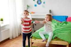 Enfants soufflant des bulles de savon et jouant à la maison Images stock