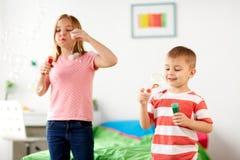 Enfants soufflant des bulles de savon et jouant à la maison Photos libres de droits