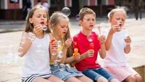 Enfants soufflant des bulles dehors Photo stock