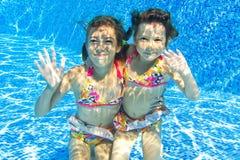 Enfants sous-marins de sourire heureux dans la piscine Photo libre de droits