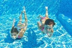 Enfants sous-marins de sourire heureux dans la piscine Image libre de droits