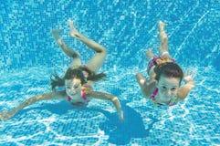 Enfants sous-marins de sourire heureux dans la piscine Photo stock