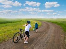 Enfants sportifs marchant vers le haut avec des vélos Photographie stock libre de droits