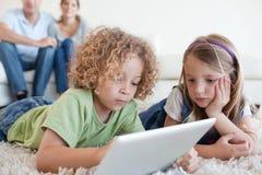 Enfants sérieux à l'aide d'un ordinateur de comprimé tandis que leurs heureux paren Image stock