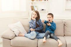 Enfants stupéfaits regardant la TV à la maison photos libres de droits