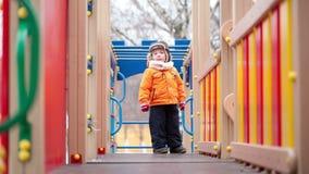 Enfants sur l'équipement de terrain de jeu Image libre de droits