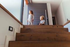 Enfants sur l'escalier regardant dehors Images libres de droits