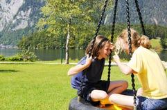 Enfants sur l'oscillation au stationnement de bord de lac Image stock