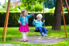 Enfants sur l'oscillation de terrain de jeu Photographie stock