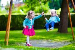 Enfants sur l'oscillation de terrain de jeu Image libre de droits