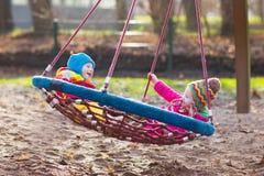 Enfants sur l'oscillation de terrain de jeu Images stock