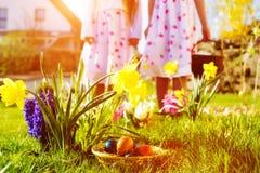 Enfants sur la chasse à oeuf de pâques avec des oeufs Photo stock