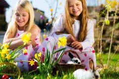 Enfants sur la chasse à oeuf de pâques avec le lapin Photographie stock