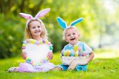 Enfants sur la chasse à oeuf de pâques Photographie stock