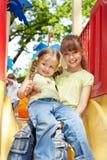 Enfants sur la glissière extérieure en stationnement. Image libre de droits