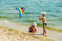 Enfants sur la plage jouant avec un cerf-volant Photos libres de droits