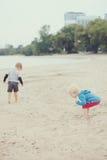 Enfants sur la plage jouant des coquillages de cueillette Images libres de droits