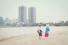 Enfants sur la plage jouant des coquillages de cueillette Image stock