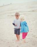 Enfants sur la plage jouant des coquillages de cueillette Photographie stock