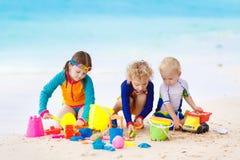 Enfants sur la plage tropicale Jouer d'enfants  en mer Images libres de droits