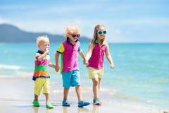Enfants sur la plage tropicale Jouer d'enfants  en mer Images stock