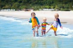Enfants sur la plage tropicale Jouer d'enfants  en mer Image stock