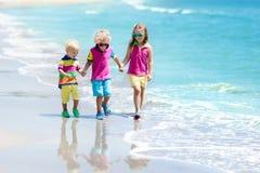 Enfants sur la plage tropicale Jouer d'enfants  en mer Image libre de droits
