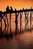 Enfants sur la silhouette de coucher du soleil de passerelle Photo libre de droits