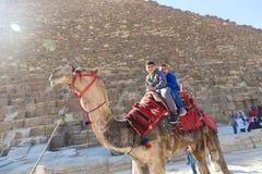 Enfants sur le chameau en pyramides de Gizeh Photographie stock libre de droits