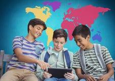 Enfants sur le comprimé devant la carte colorée du monde Image libre de droits