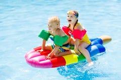 Enfants sur le flotteur gonflable dans la piscine Image libre de droits