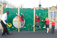 Enfants sur le mur s'élevant dans le terrain de jeu d'école chez Breaktime Images stock