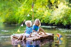 Enfants sur le radeau en bois Image libre de droits