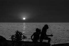 Enfants sur le rivage de coucher du soleil Image libre de droits