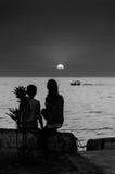 Enfants sur le rivage de coucher du soleil Photo stock