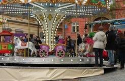 Enfants sur le rond point sur le marché de Noël Photo libre de droits