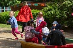 Enfants sur le terrain de jeu dans l'école maternelle Photos stock
