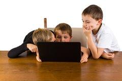 3 enfants sur un ordinateur portable Photographie stock libre de droits