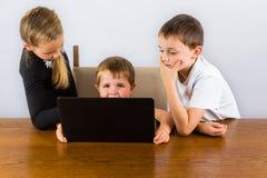 3 enfants sur un ordinateur portable Photo libre de droits