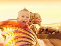 Enfants sur un tour de montagnes russes d'été Photos stock