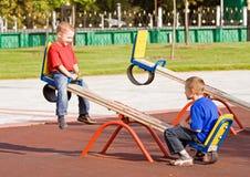 Enfants sur une balançoir Image libre de droits