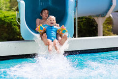 Enfants sur une glissière d'eau dans la piscine Images libres de droits