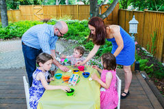 Enfants teignant des oeufs de pâques avec la mère et le père Images libres de droits